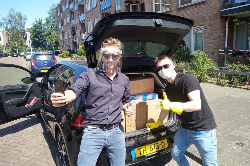 Two alumni loading packages into a car wearing PPE