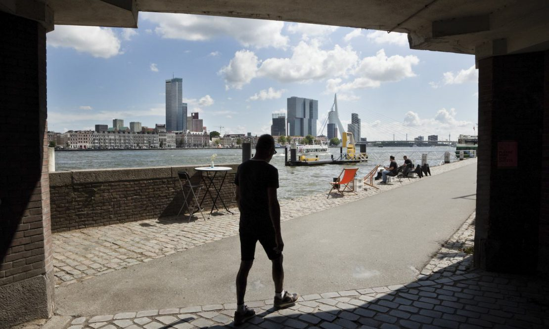 A person walks past the harbour in Rotterdam