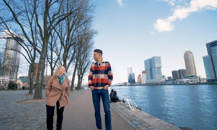 Two people walking past a view of Rotterdam