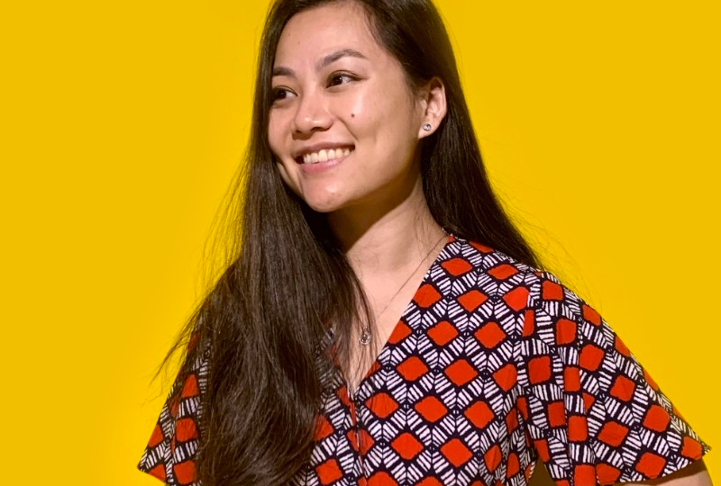 Picture of Micky Chen smiling on a yellow background